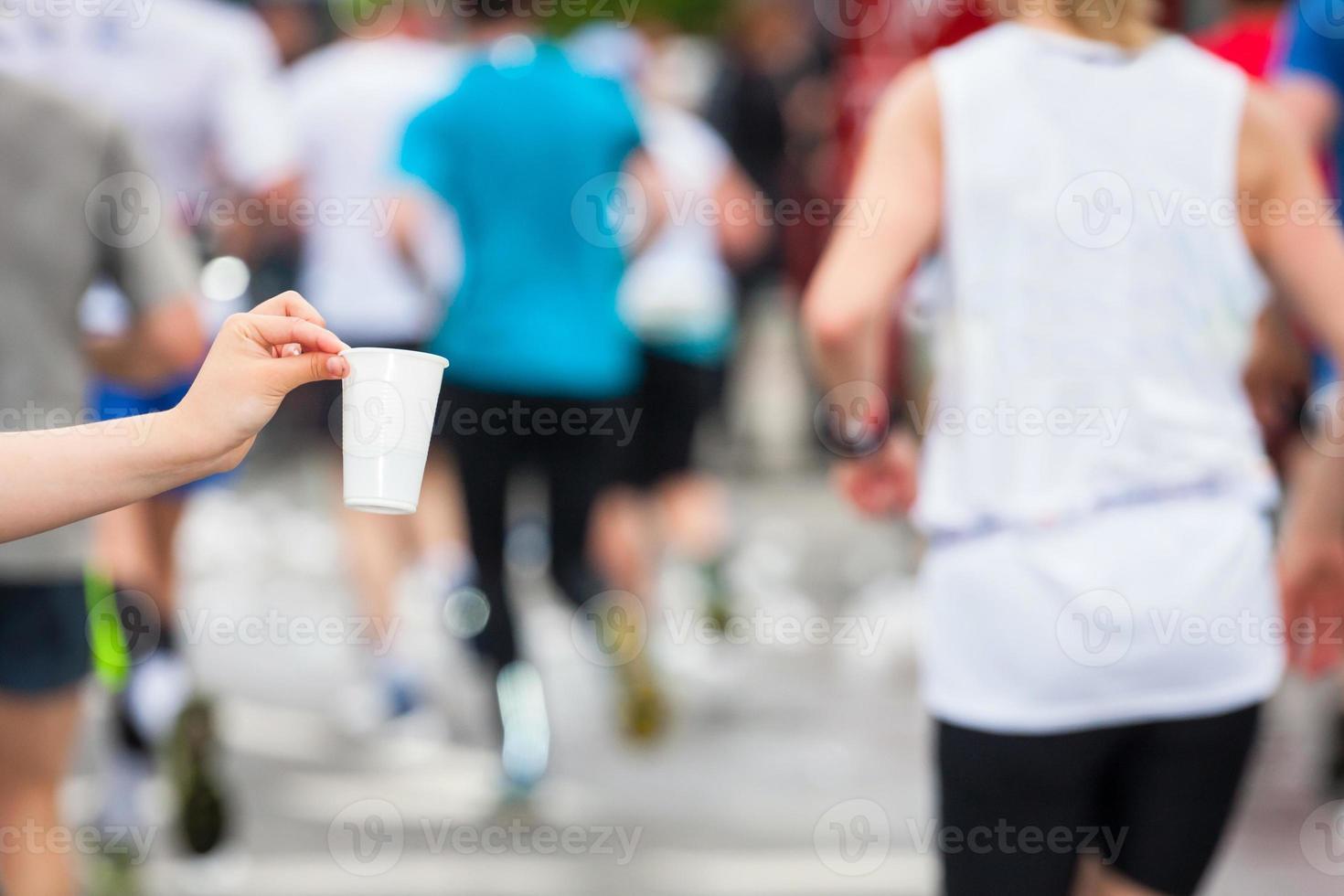 Marathon runner picking up water at service point photo