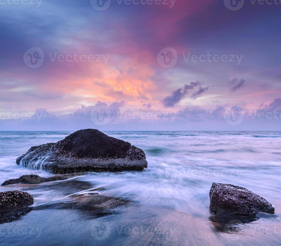 Waves and rocks on beach of sunset photo