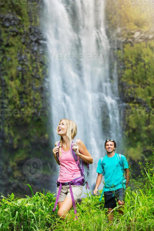 Couple hiking to waterfall photo