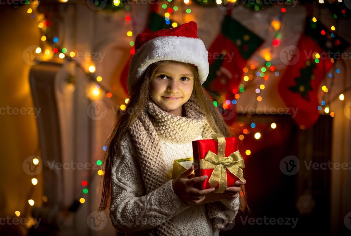 Retrato de niña sonriente abriendo caja de regalo brillante en Navidad foto