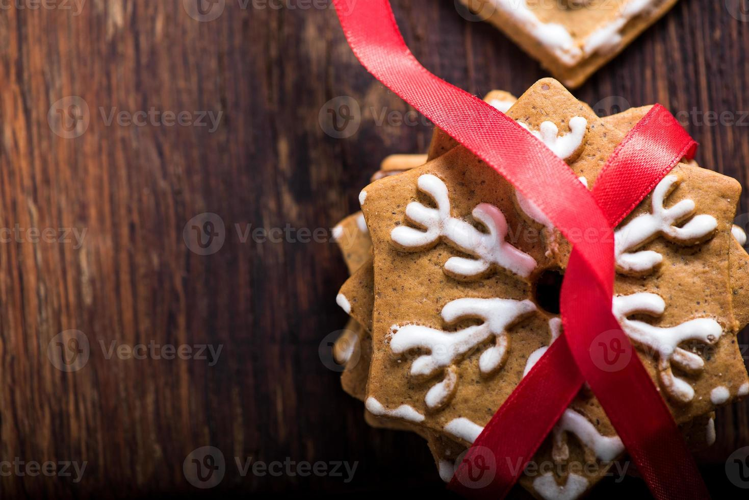 Gingerbread cookies with red ribbon on wooden background photo
