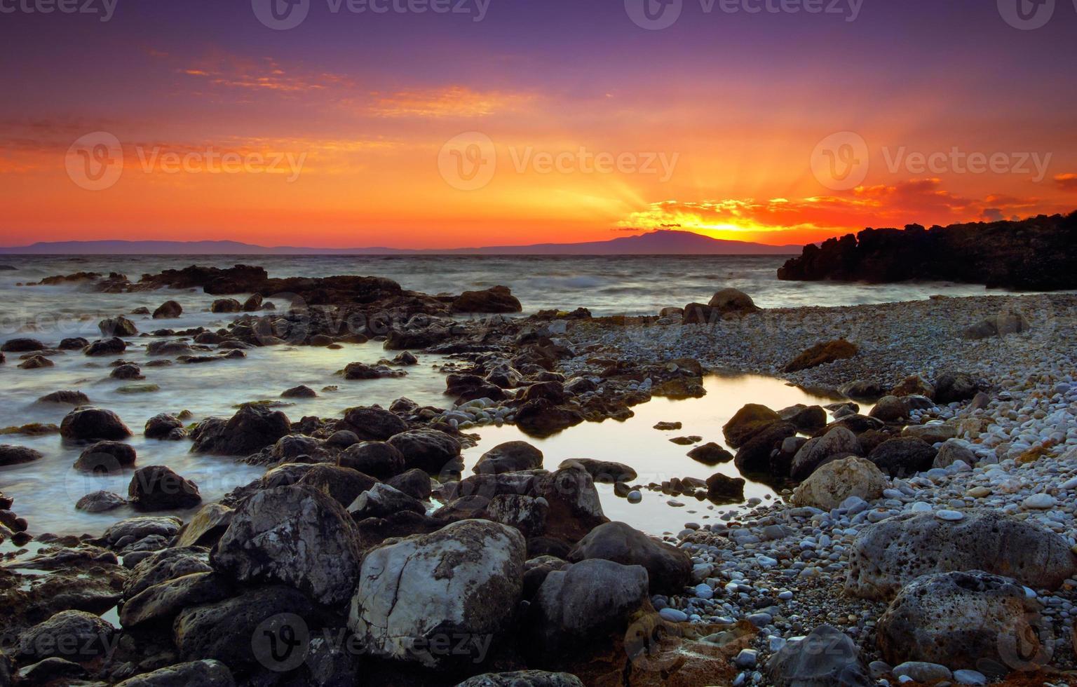 Glorious sunset over rocky sea photo