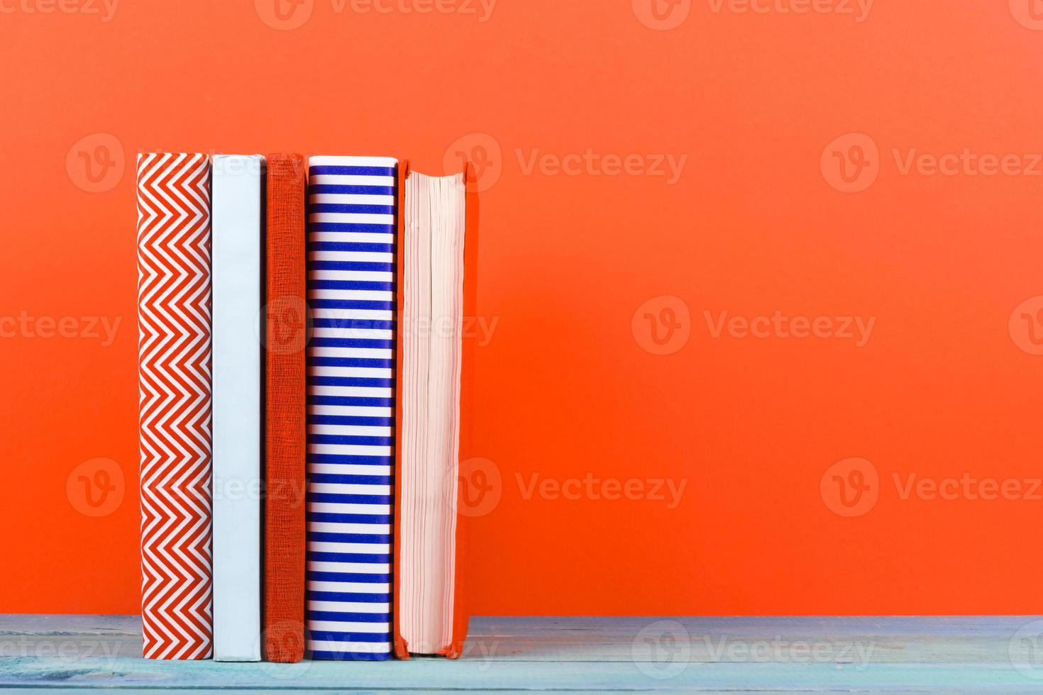 Row of colorful hardback books, open book on red background photo