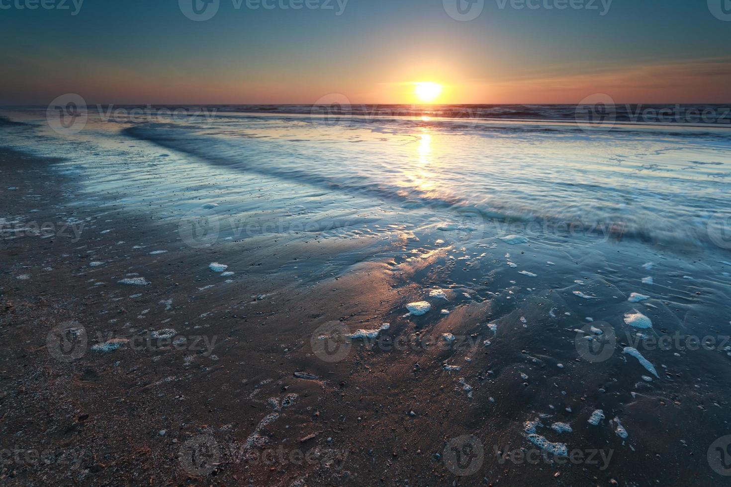 puesta de sol sobre la playa de arena del mar del norte foto