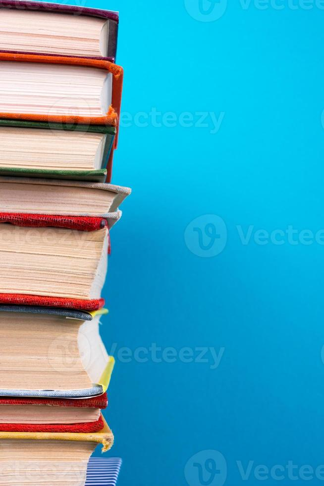 Stack of colorful hardback books, open book on blue background photo