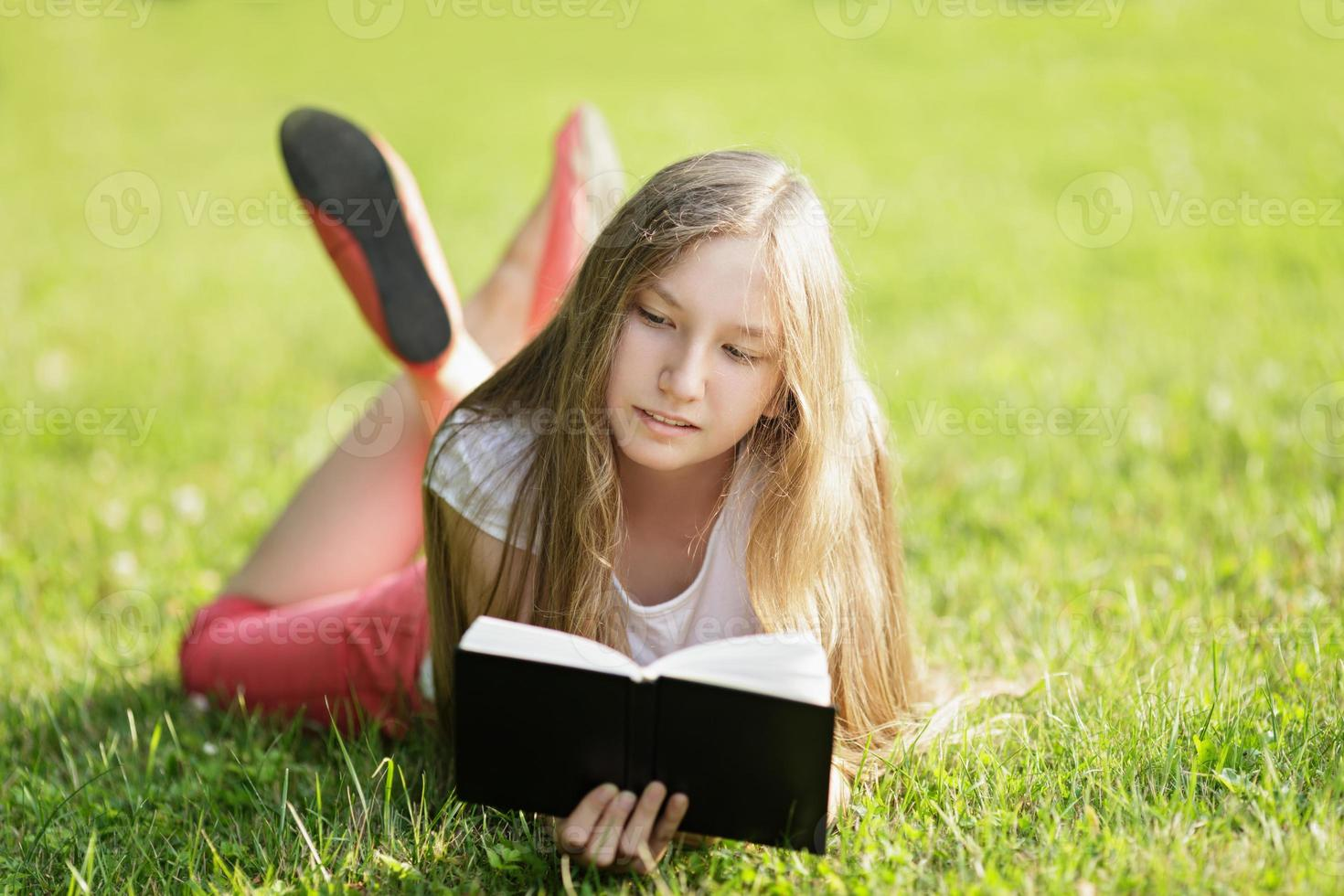young girl reading book lying on the grass photo