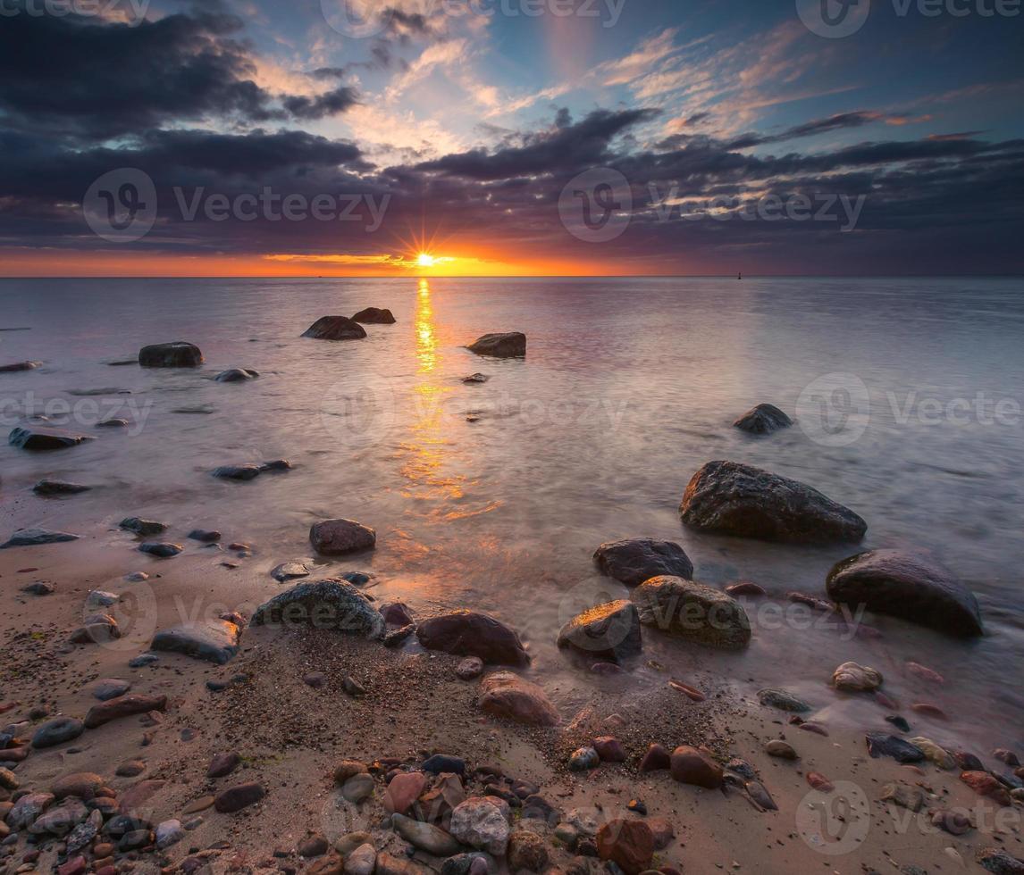 Rocky sea shore at sunrise. Beautiful seascape photo