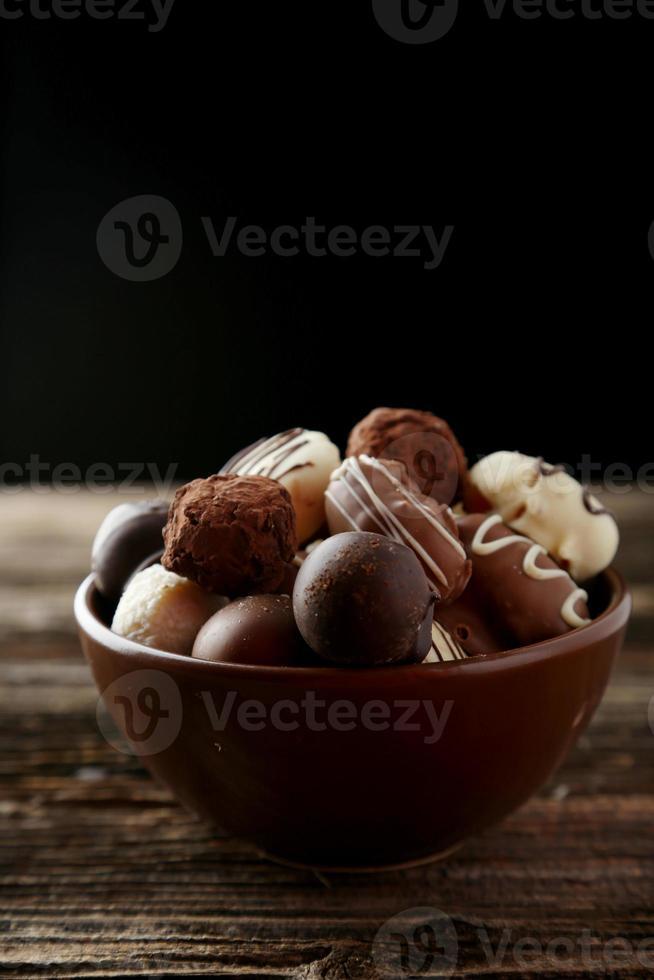 chocolates em uma tigela com fundo de madeira marrom foto