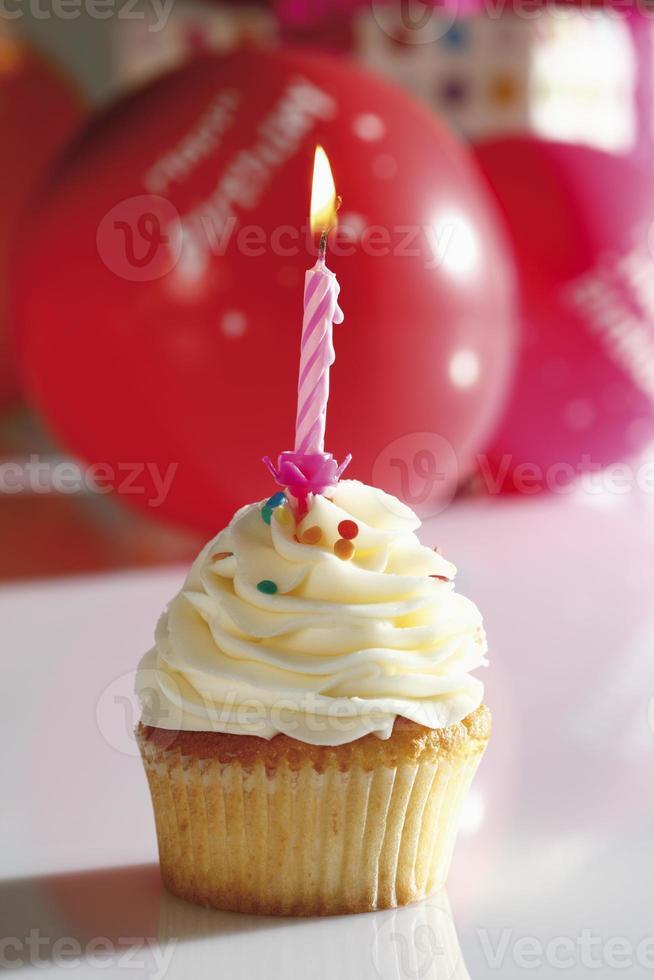 Close up di crema al burro alla vaniglia cupcake con candela di compleanno foto
