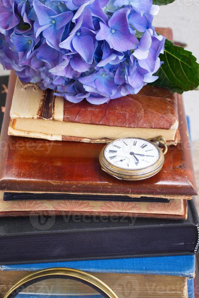 pilha de livros antigos com flores e relógio foto