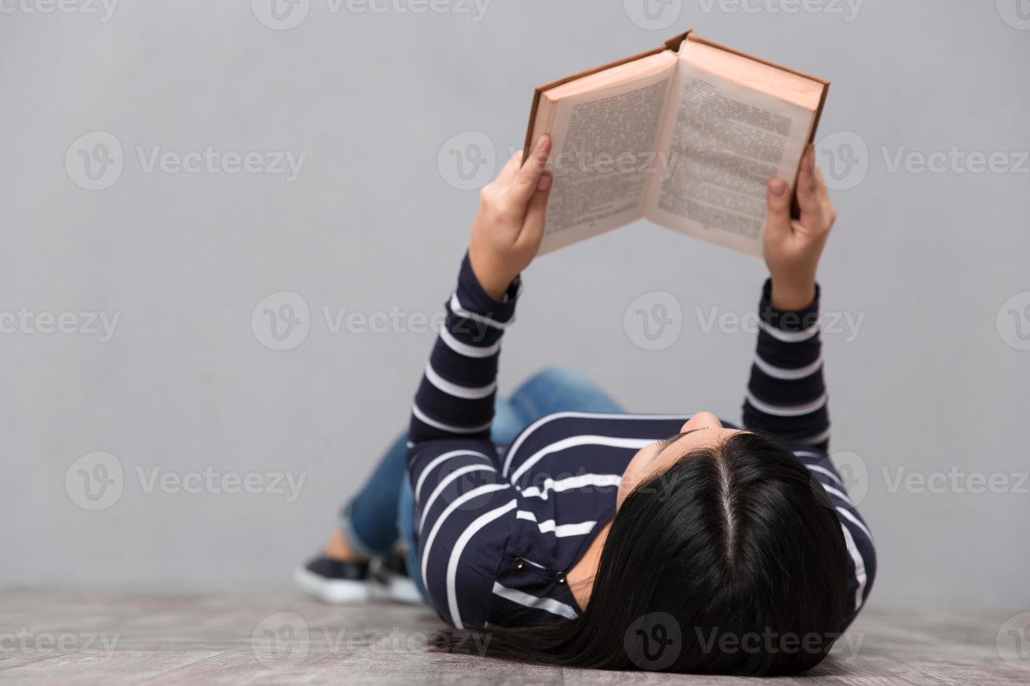 jonge vrouw liegen en lezen van een boek foto