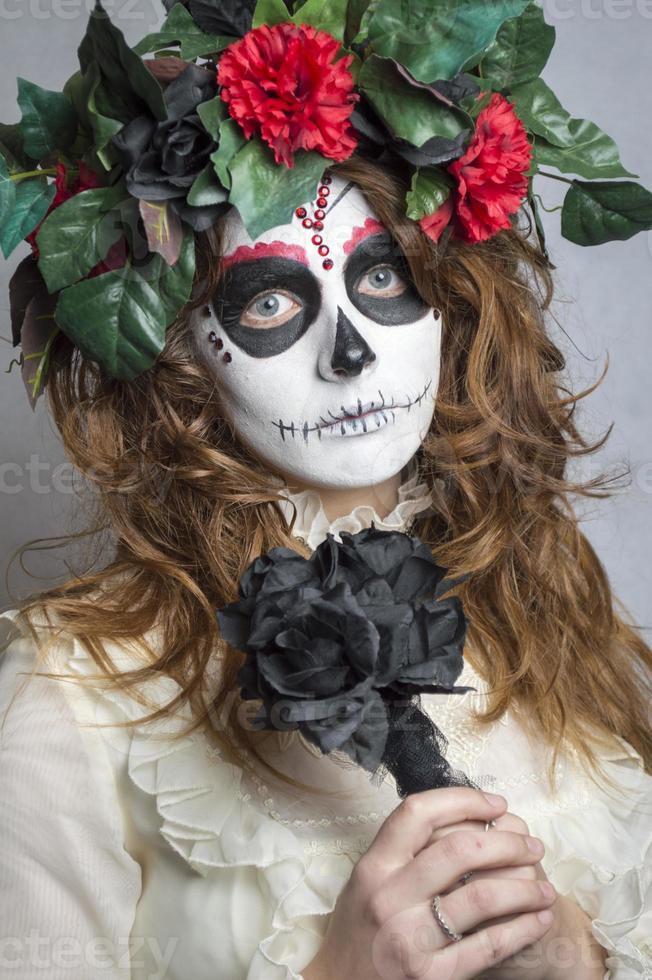 aantrekkelijke jonge vrouw met de make-up en de bloemen van de suikerschedel foto