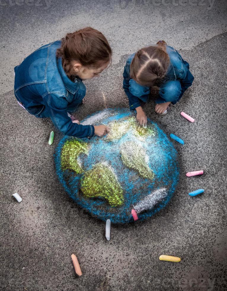 zwei Mädchen, die realistisches Erdbild mit Kreiden auf Boden zeichnen foto