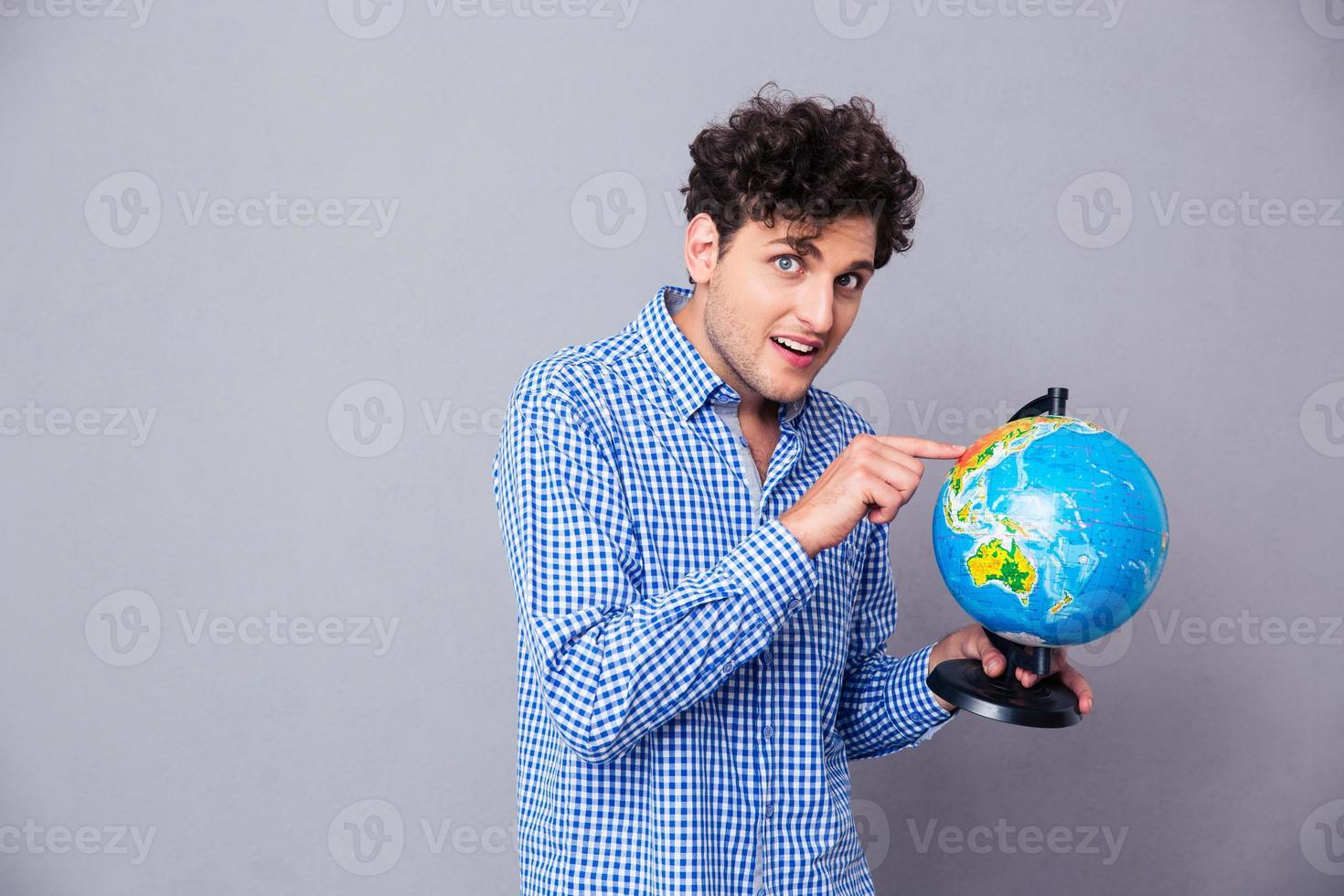 homme heureux, doigt pointé, globe photo