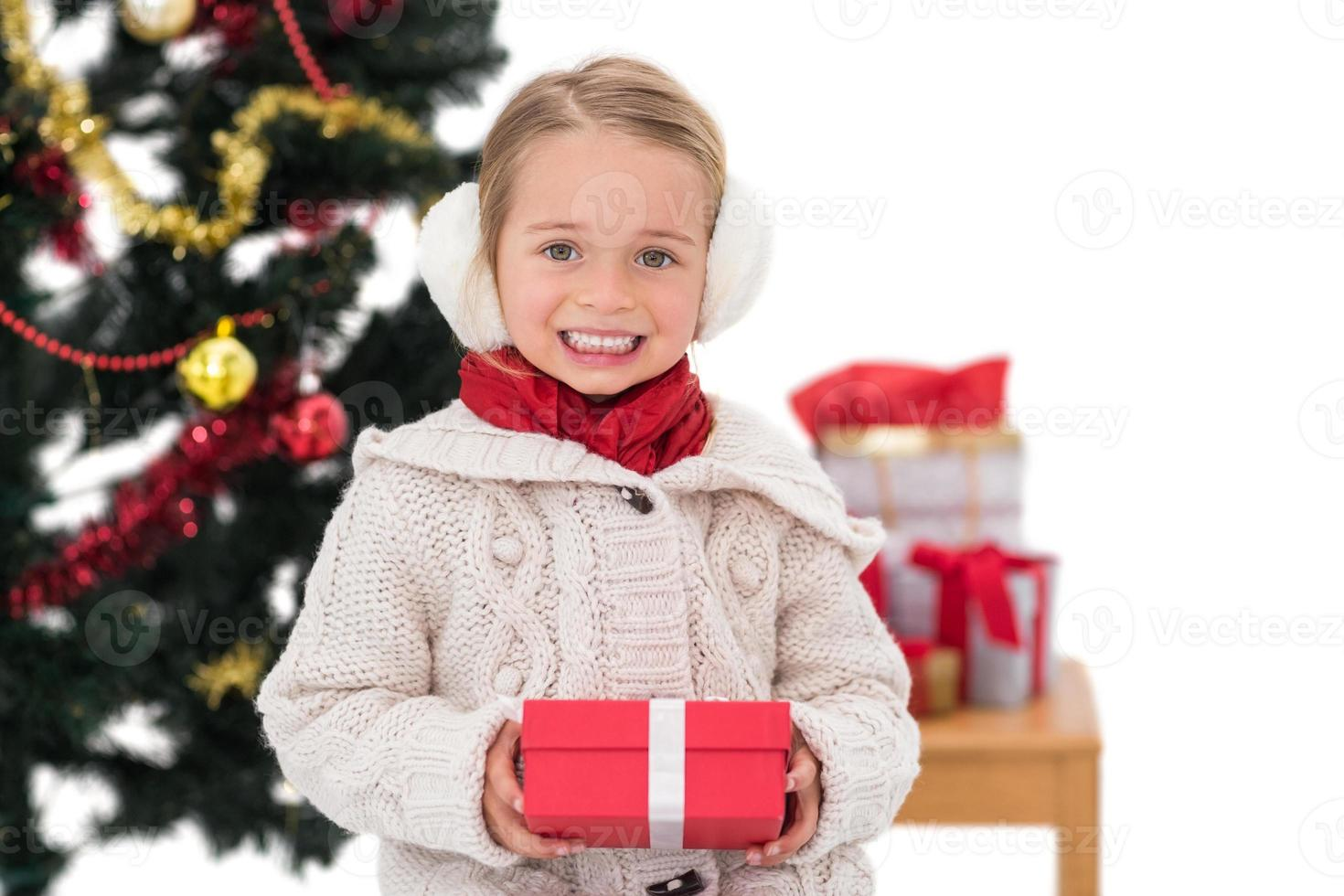 niña festiva sosteniendo un regalo foto