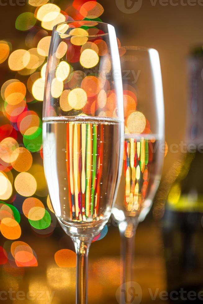 due bicchieri di champagne contro un albero di Natale scintillante foto