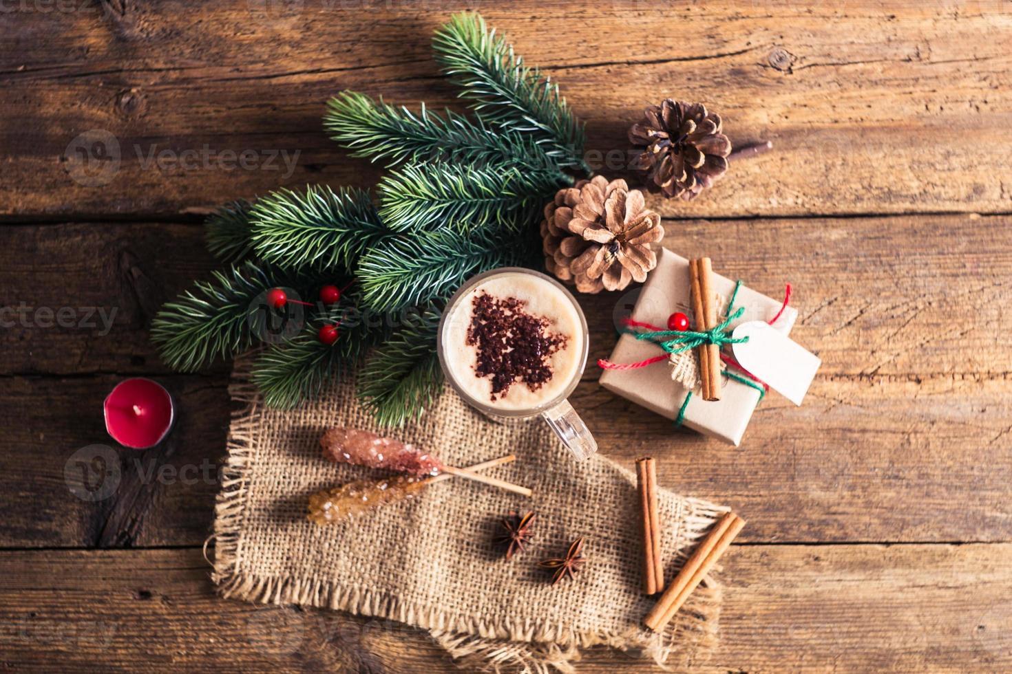 Kakao auf einem Holztisch mit Weihnachtsschmuck, Zweigen, Gewürzen foto
