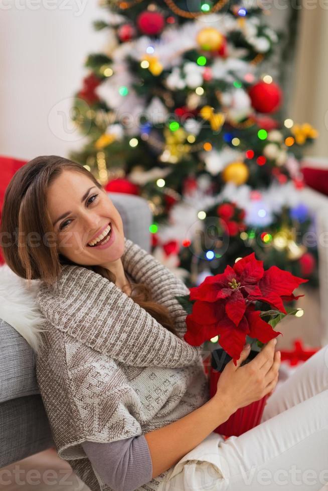 lächelnde Frau mit Blume, die nahe Weihnachtsbaum sitzt foto