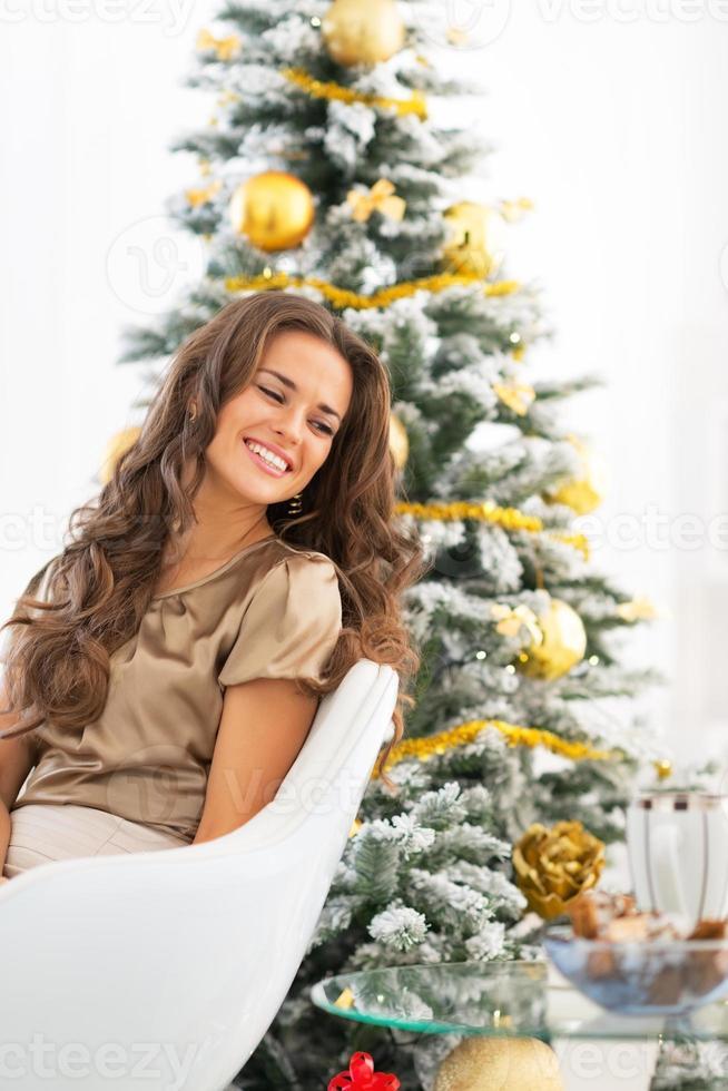 Porträt der glücklichen jungen Frau, die nahe Weihnachtsbaum sitzt foto