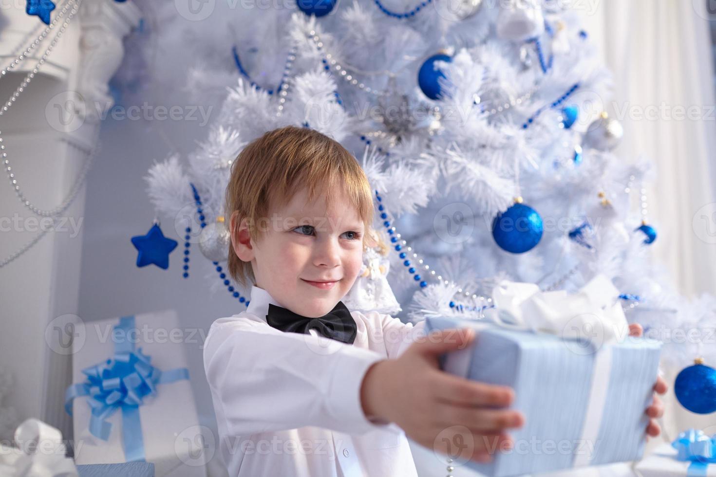 menino de camisa e gravata borboleta dando um presente foto