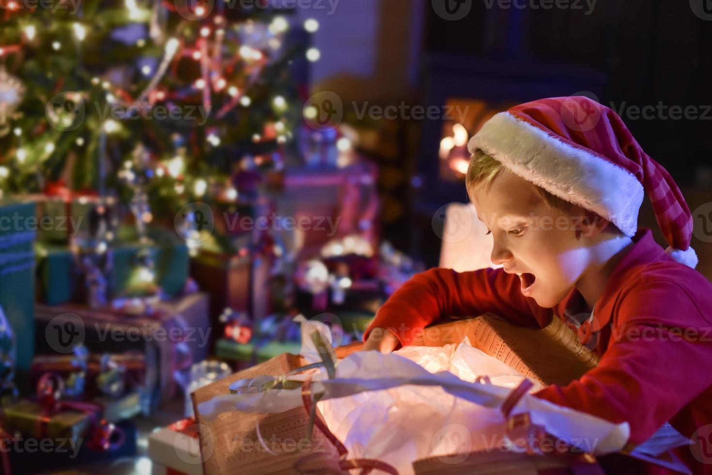 época de natal, garotinho abrindo um presente perto de uma árvore foto