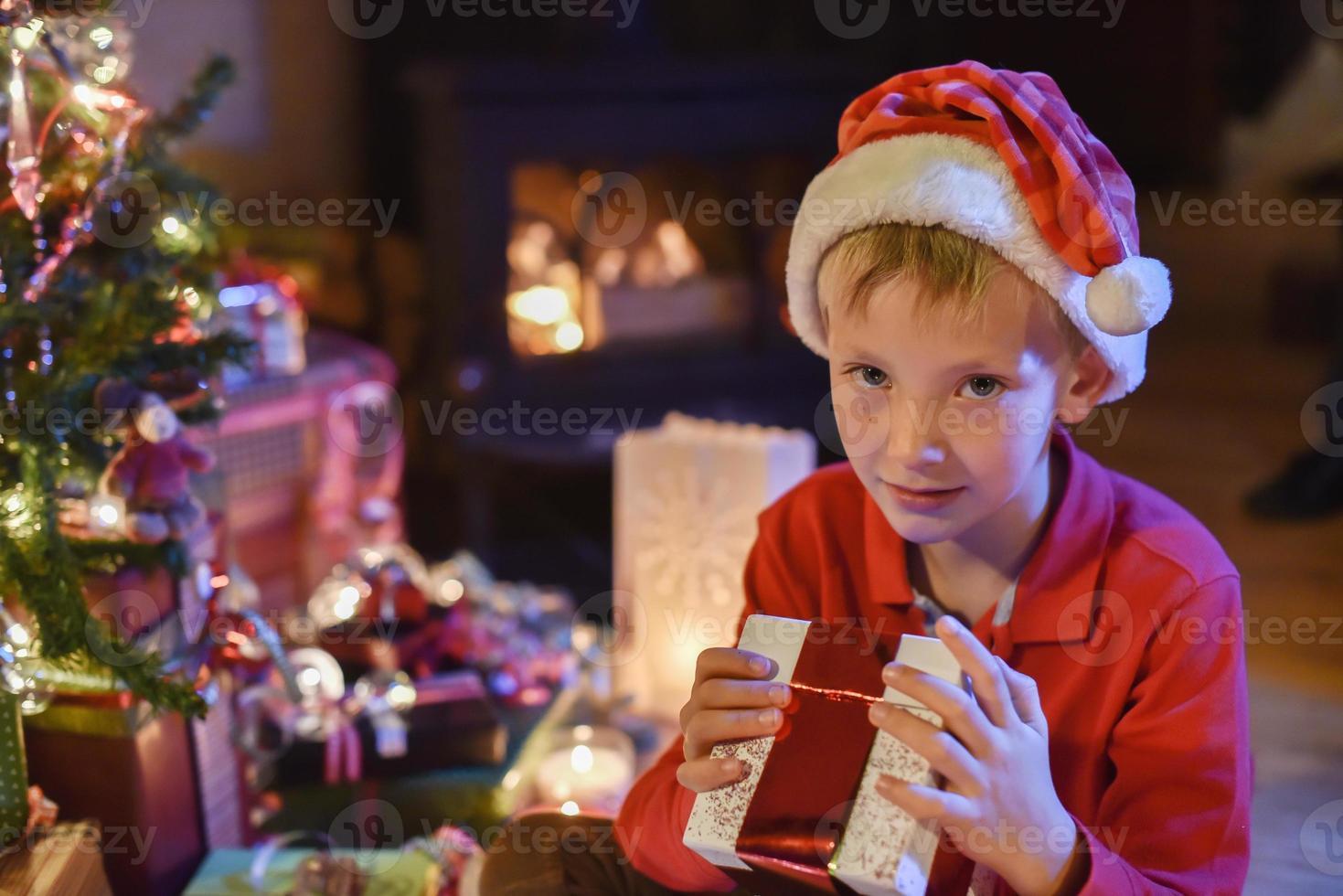 Noël, petit garçon ouvrant un cadeau près de l'arbre illuminé photo