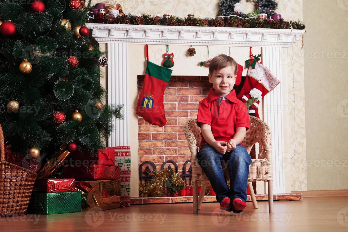 menino feliz na frente da árvore de natal esperando foto