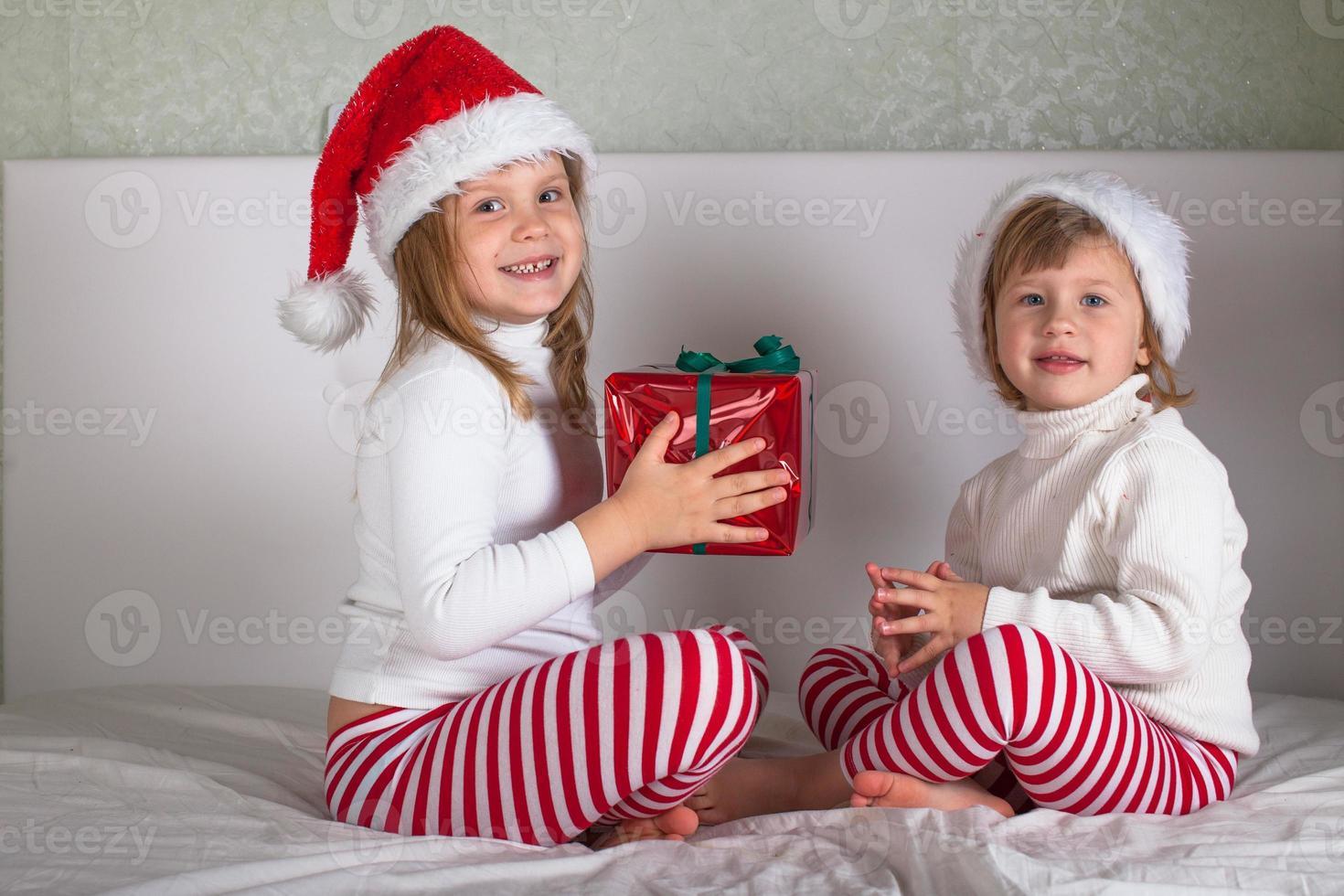 enfants drôles en pyjama et bonnet de Noël photo
