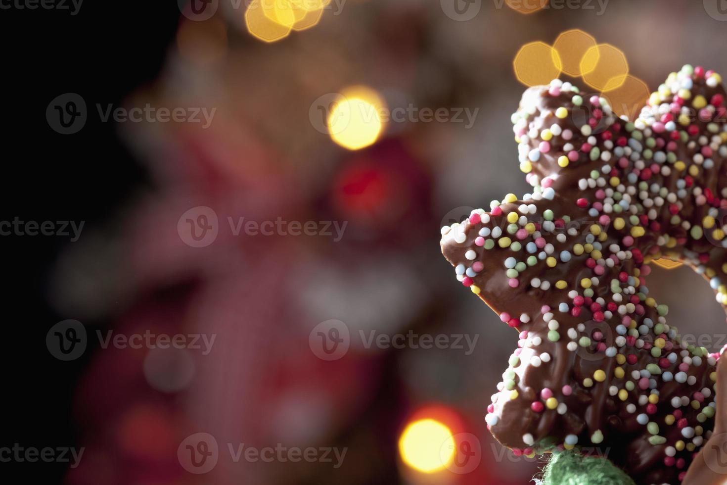 estrella de chocolate delante del árbol de navidad foto