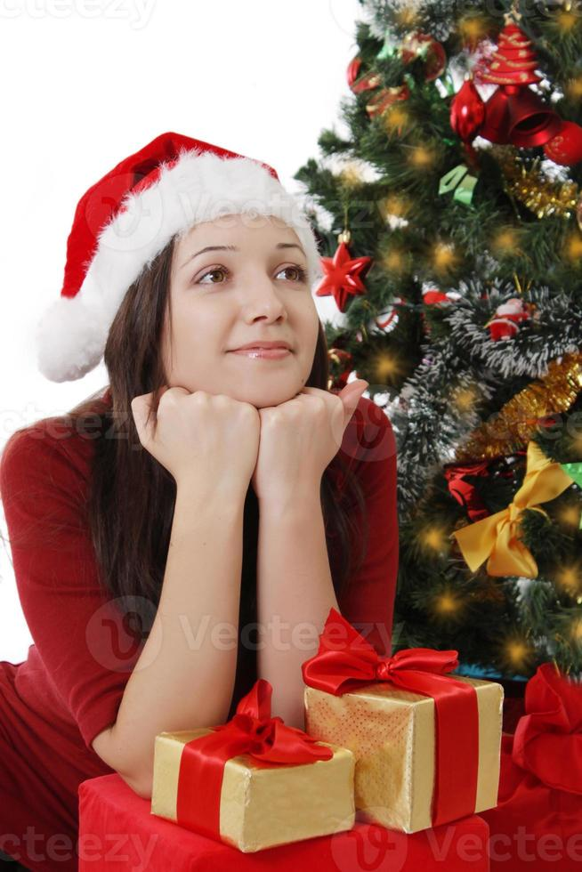 Dreaming girl with gifts sitting under Christmas tree photo