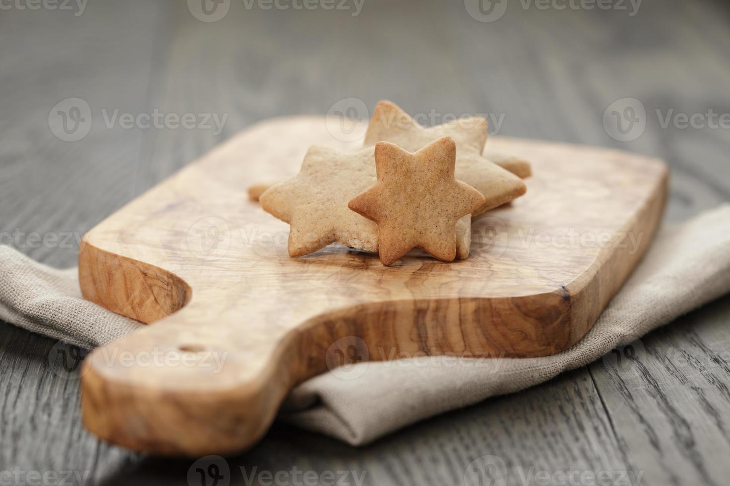 Galletas de jengibre en forma de estrella caseras en tablero de oliva foto