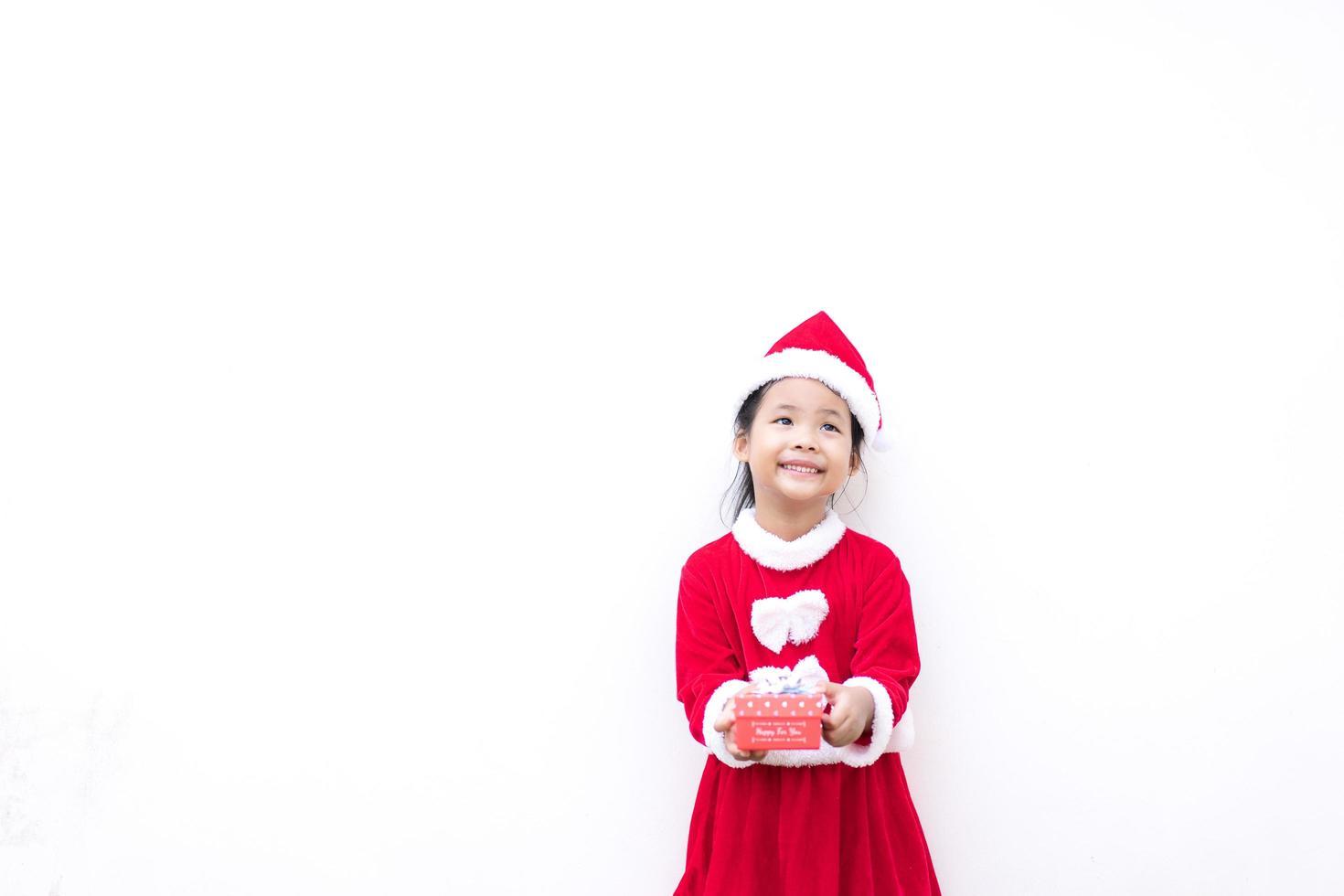 niña asiática en traje rojo de santa claus foto
