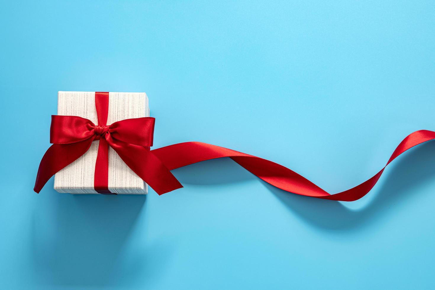 Caja de regalo con lazo rojo sobre fondo azul. foto