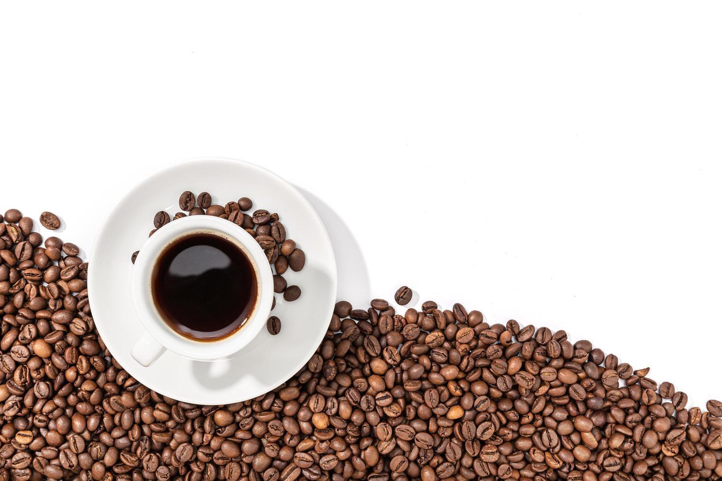 Taza de café expreso y granos tostados sobre fondo blanco. foto