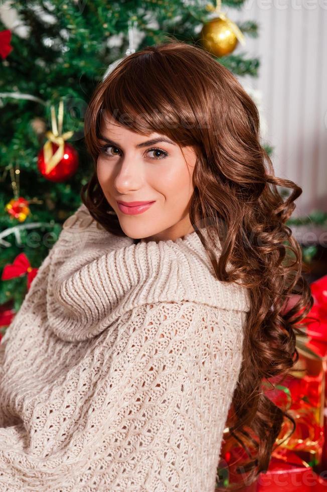 Retrato de mujer joven sonriente cerca del árbol de navidad foto