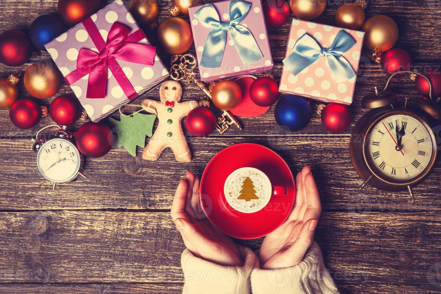 Mujer sosteniendo una taza de café cerca de regalos de Navidad foto