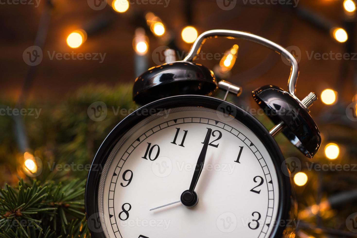 árbol de navidad, luces y reloj sobre la pared de madera foto