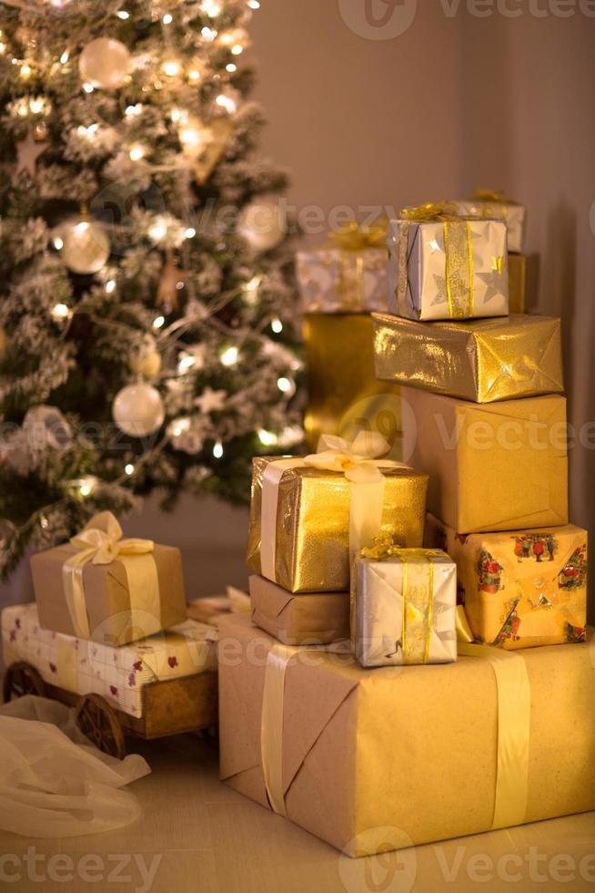 regalos de navidad de oro y plata debajo del árbol de navidad, foto