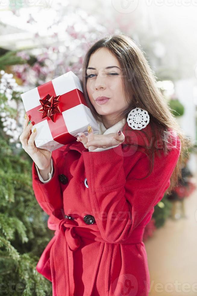 Mujer joven muestra sus paquetes de regalo dentro de una tienda de Navidad foto