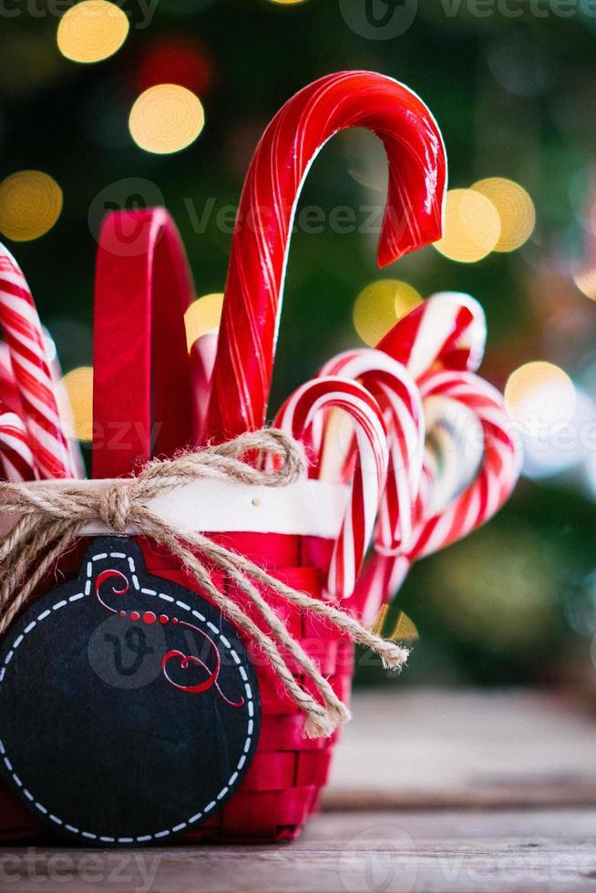 Bastones de caramelo en una canasta sobre fondo de Navidad foto