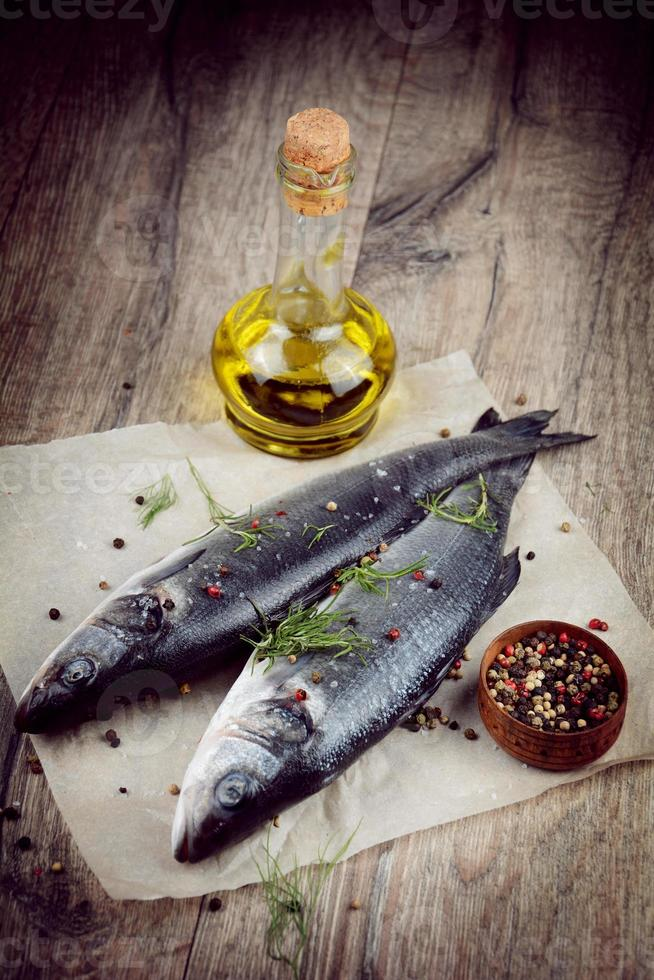 Raw seabass fish on the wooden board photo