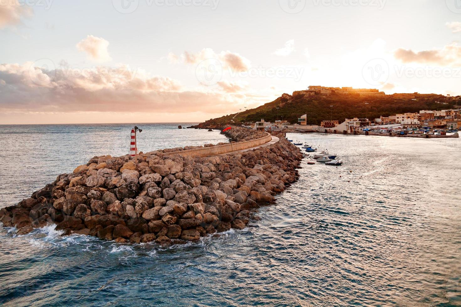 Entrance in bay, seafront with lighthouse, Gozo, Malta. photo