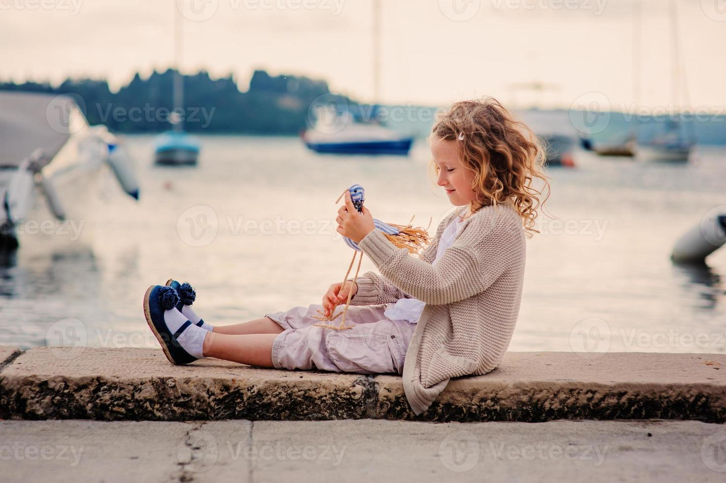 child girl playing with toy bird on seaside photo