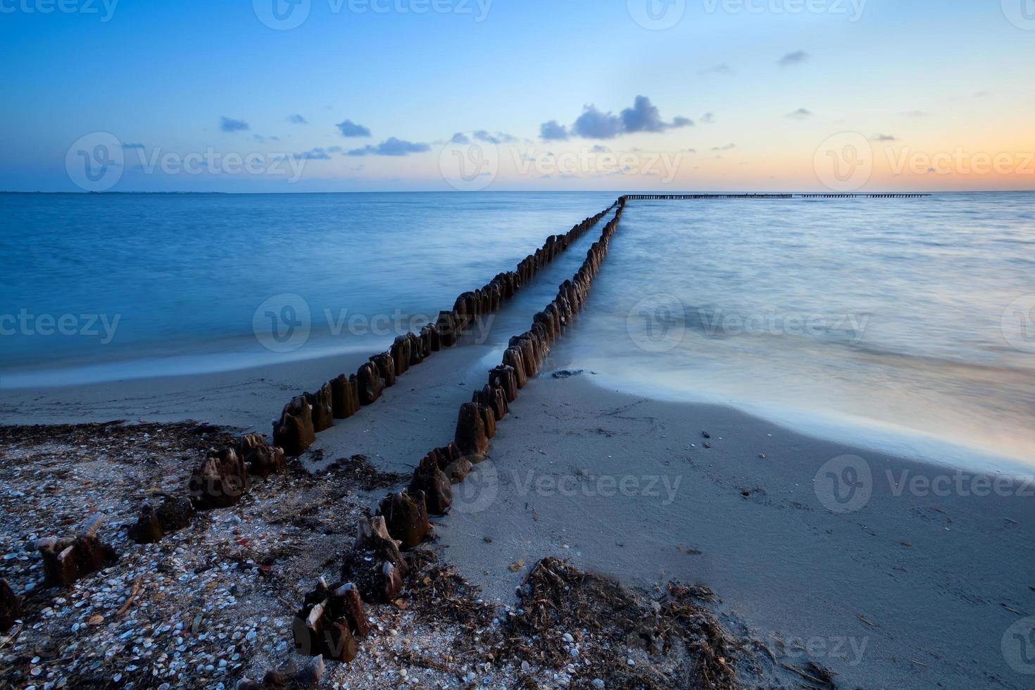 Largo rompeolas de madera en el mar del norte foto
