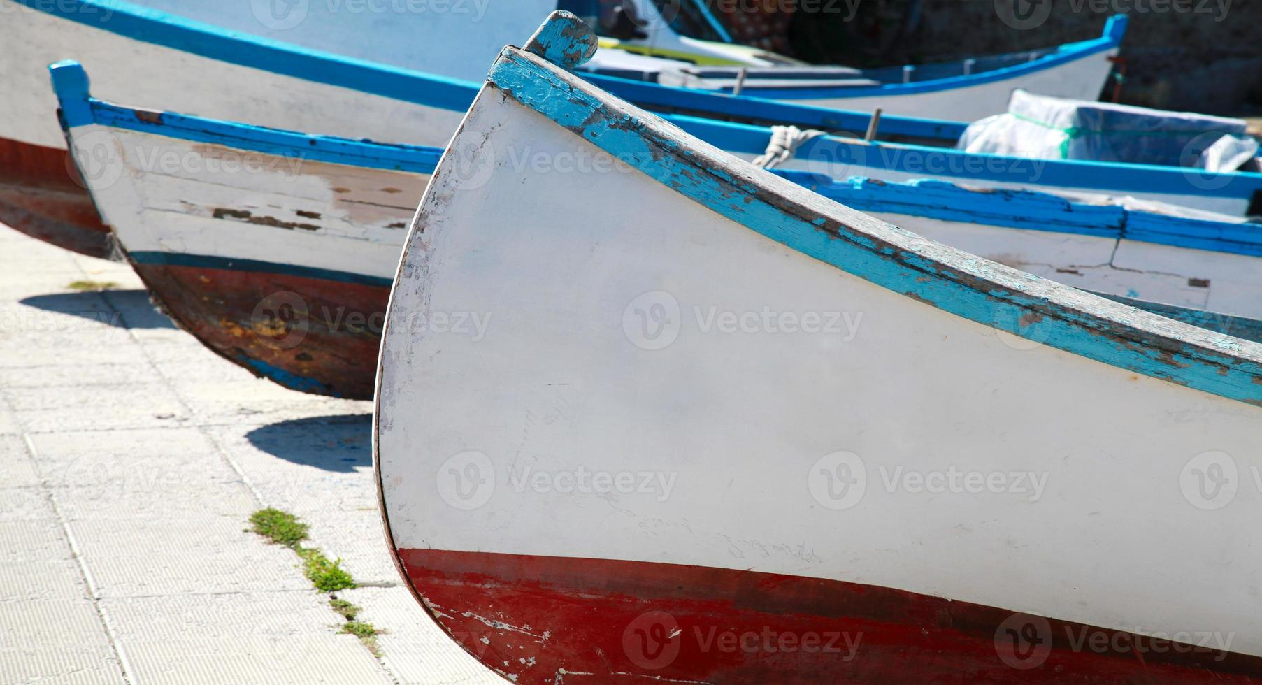 Old wooden fishing boats are laying on the sea coast photo