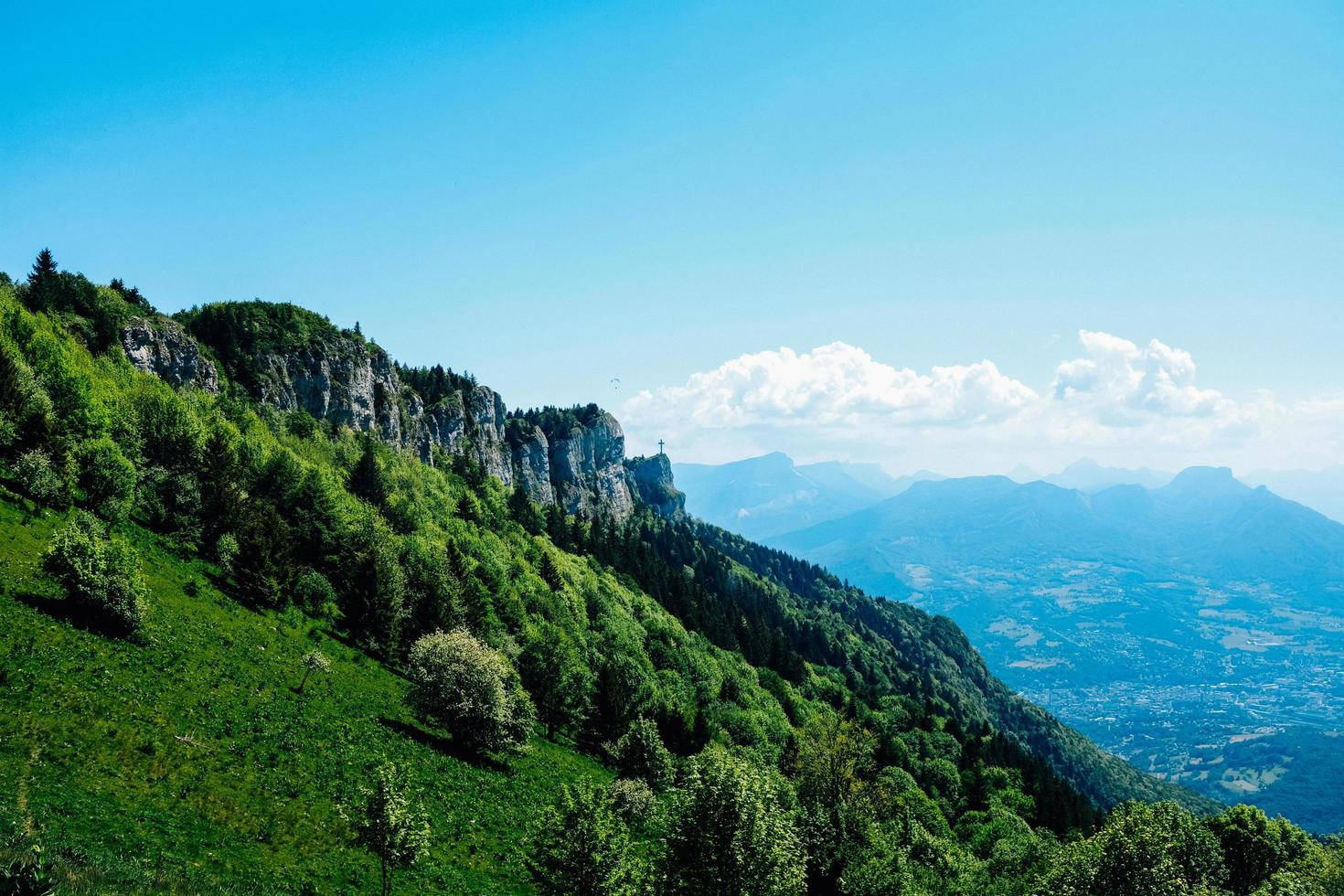 Green trees on mountain under blue sky photo