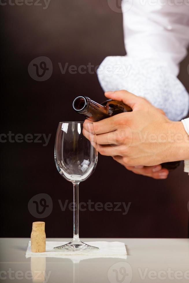 Man waiter pouring white wine into glass. photo