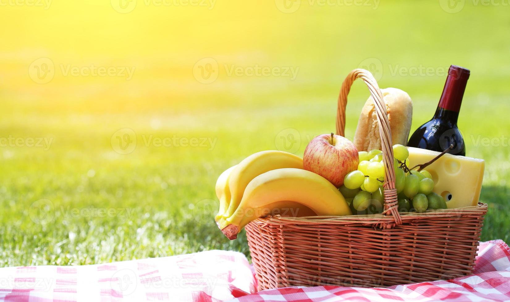 Picnic basket with food on grass photo