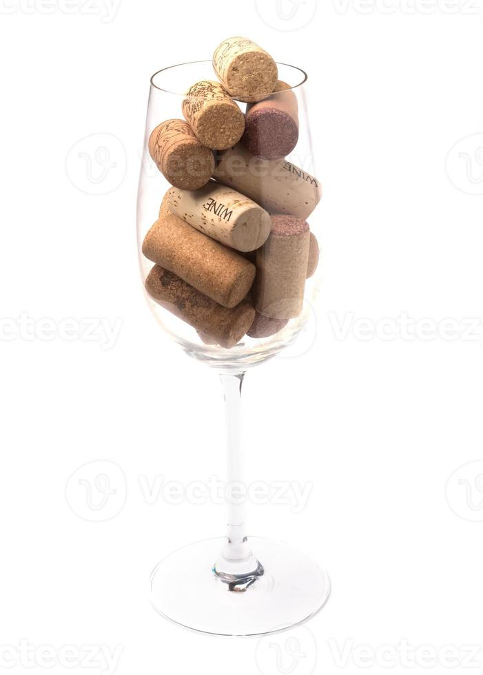 Wine glass filled with wine corks photo