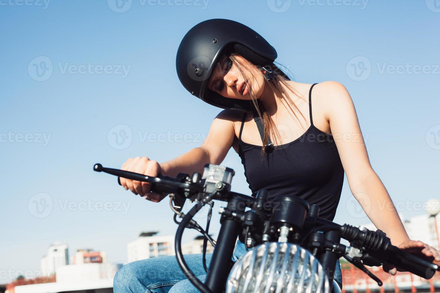 Biker girl sitting on vintage custom motorcycle photo